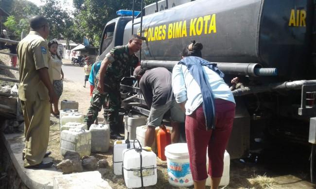 Babinsa Koramil Rasanae Bantu Distribusi Air Bersih Untuk Warga