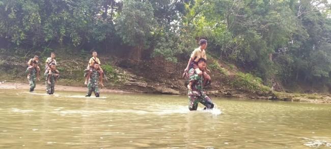 Demi Menuntut Ilmu, Satgas Yonif R 142/KJ Pikul Anak-Anak Sekolah Sebrangi Sungai Telau