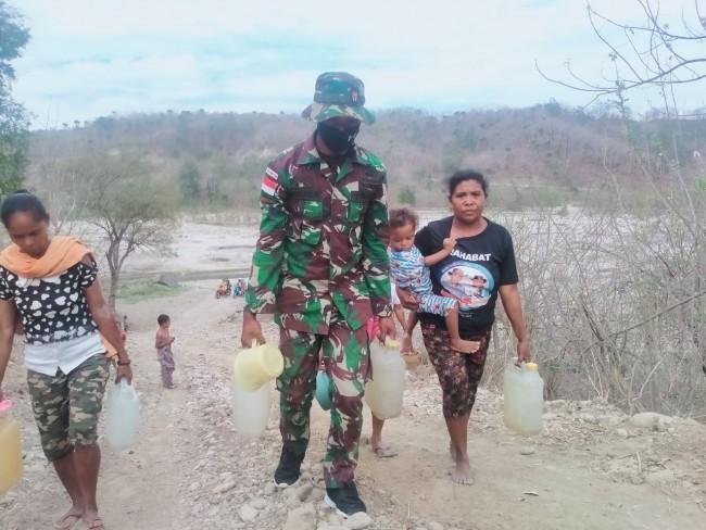 Personil Pos Asulait Satgas Yonif RK 744/SYB Membantu Masyarakat Mengambil Air Bersih
