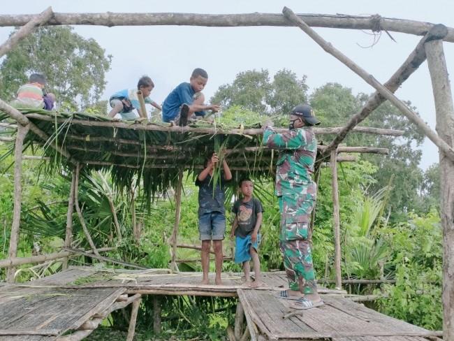 Personel TNI bersama Sekelompok Siswa Perbatasan Bangun Pos Kamling